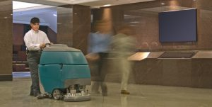 image of a man using a walk behind auto scrubber
